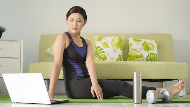 Jonge vrouw die yoga beoefent op zoek naar ideeën van laptop thuis
