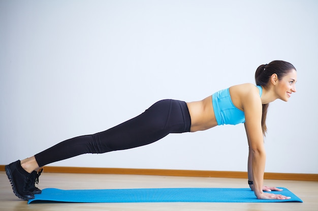 Jonge vrouw die yoga beoefent, wild thing doet, flip-the-dog oefening, camatkarasana pose, trainen, het dragen van sportkleding, zwarte broek en top, indoor volledige lengte, grijze muur in yogastudio
