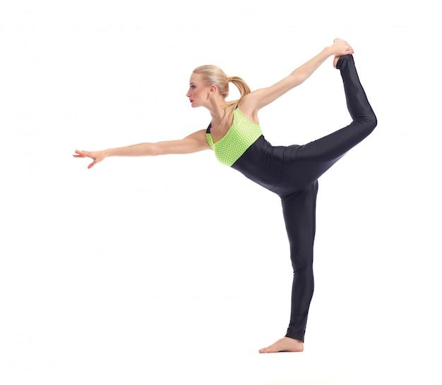 Jonge vrouw die yoga bij het witte in evenwicht brengen op één been doet