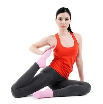 Jonge vrouw die yoga doet die op wit wordt geïsoleerd