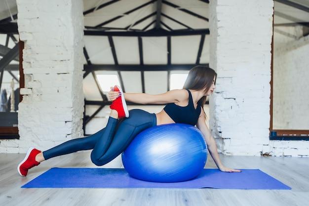 Jonge vrouw die yoga doet en zich uitstrekt op blauwe bal bij witte sportschool
