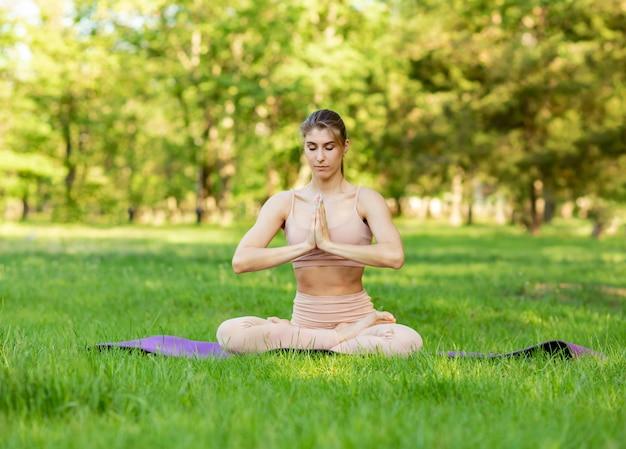 Jonge vrouw die yoga doet. kaukasisch meisje dat yoga in aard uitoefent