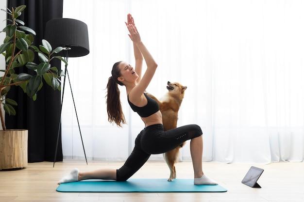 Jonge vrouw die yoga doet naast haar hond