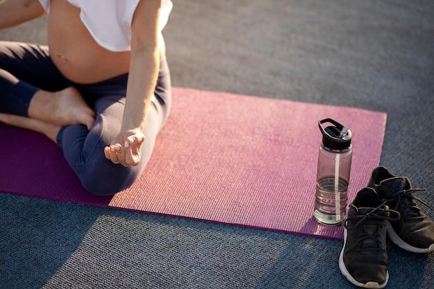 Jonge vrouw die yoga doet tijdens de zwangerschap