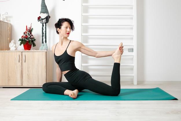 Jonge vrouw die yoga in haar eigen appartement uitoefent en geniet van haar dag