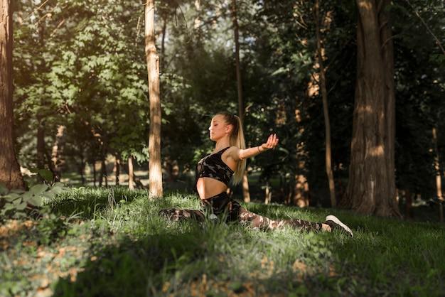 Jonge vrouw die yoga in het park doet