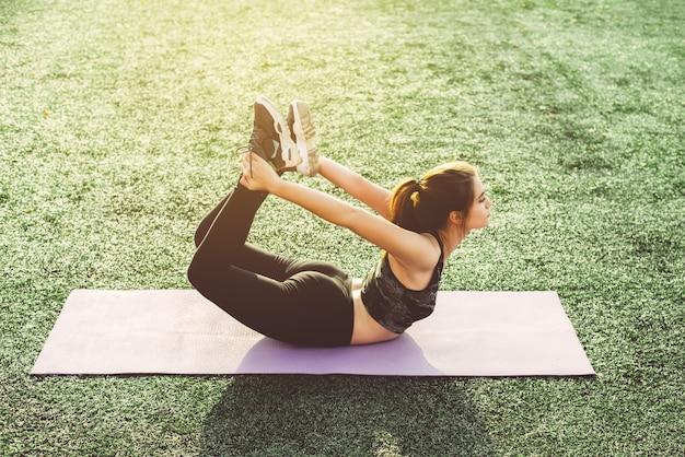 Jonge vrouw die yoga in stadion doet
