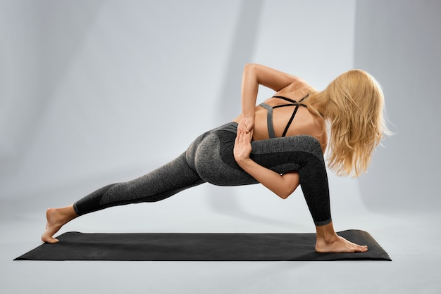 Jonge vrouw die yoga of pilates doet