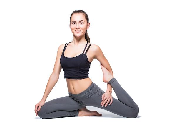 Jonge vrouw die yoga op witte achtergrond doet
