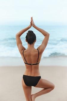 Jonge vrouw die yoga uitoefent op het strand
