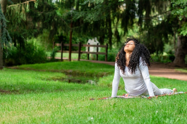 Jonge vrouw die yogahoudingen beoefent in het park omringd door bomen