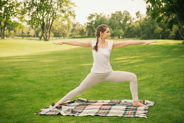 Jonge vrouw die yogaoefeningen in de aard doet