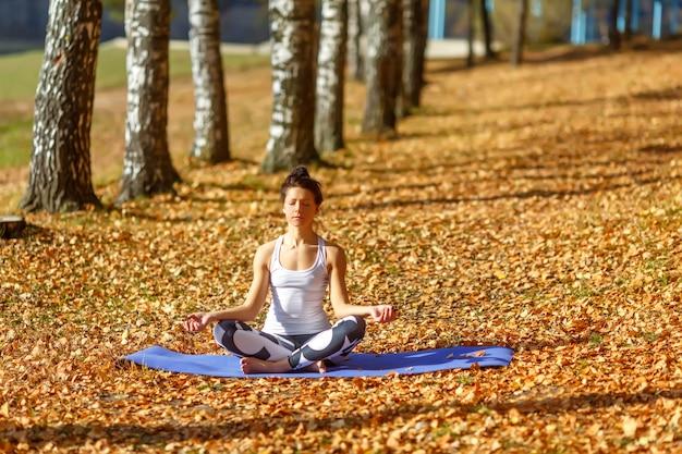 Jonge vrouw die yogaoefeningen in het park van de de herfststad doet. gezondheid levensstijl concept.