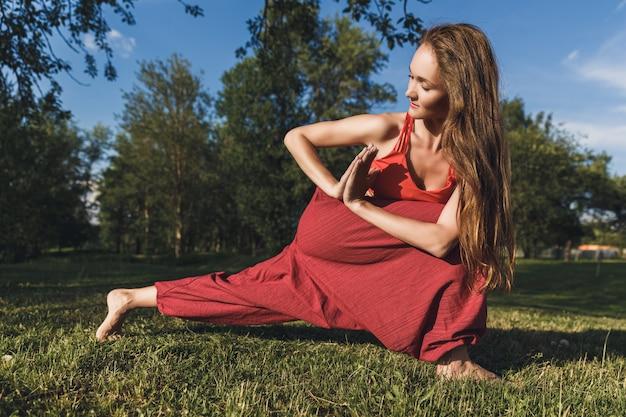 Jonge vrouw die yogaoefeningen in het park van de de zomerstad doet