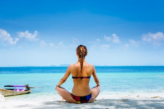 Jonge vrouw die yogaoefeningen op het overzeese strand doet
