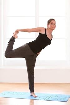Jonge vrouw die yogaoefeningen thuis doet
