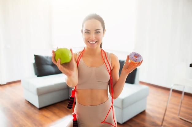 Jonge vrouw die yogatraining in ruimte doen tijdens quarantaine. het vrolijke positieve meisje houdt groene appel en hamburger in handen. moeilijke keuze. toon groene appel dichterbij.