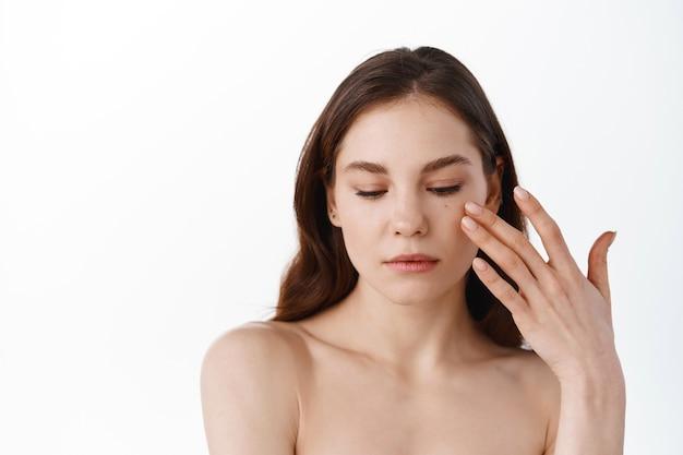 Jonge vrouw die zachtjes de zachte en gehydrateerde huid op het gezicht aanraakt, vochtinbrengende crème of huidverzorgingscosmetica aanbrengt, natuurlijke make-up draagt, met blote schouders staat, witte muur