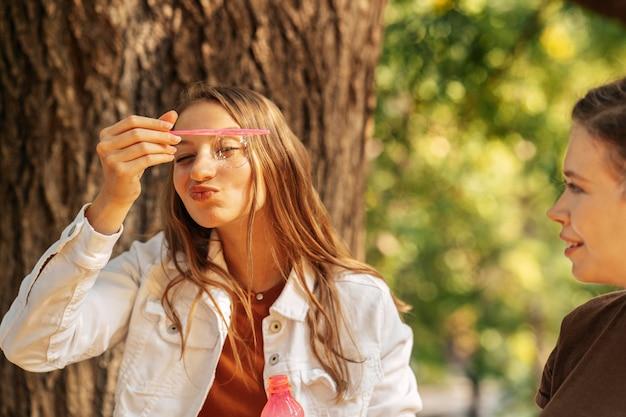 Jonge vrouw die zeepbellen naast haar vriend maakt