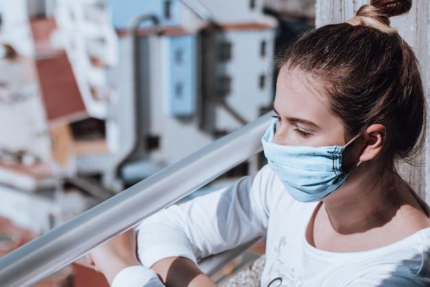 Jonge vrouw die zelfgemaakt masker draagt wegens medisch maskertekort bij quarantaine. portret van een vrouw zelf geïsoleerd tijdens covid pandemie kijken stad. masker gemaakt van zakdoek, tekort aan medisch masker