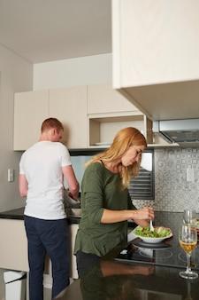 Jonge vrouw die zelfgemaakte salade mengt wanneer haar vriendje de afwas doet in de gootsteen