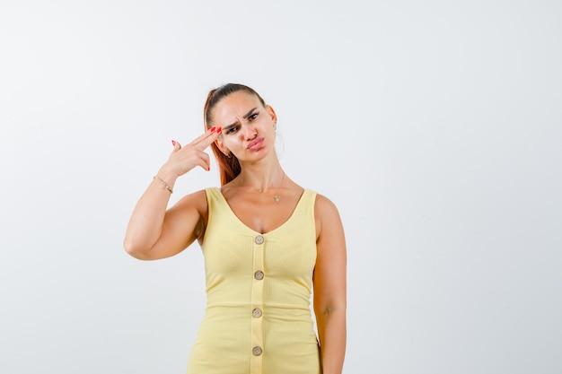 Jonge vrouw die zelfmoordgebaar in gele kleding toont en peinzend, vooraanzicht kijkt.