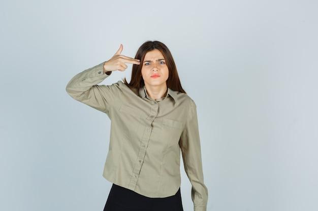 Jonge vrouw die zelfmoordgebaar maakt in shirt, rok en boos kijkt, vooraanzicht.