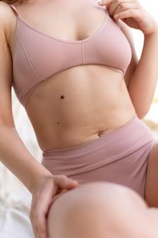 Jonge vrouw die zelfverzekerd in lingerie poseert