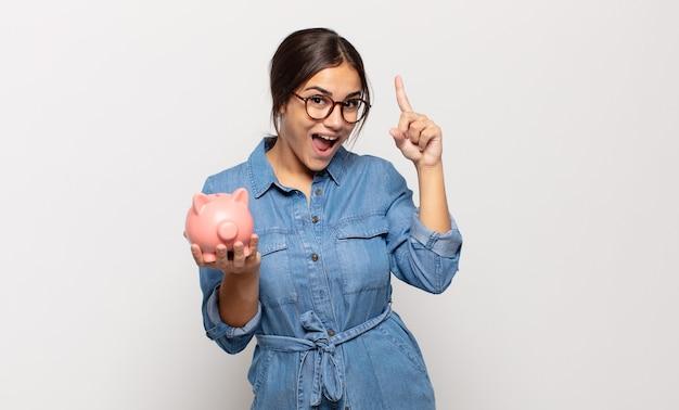 Jonge vrouw die zich als een blij en opgewonden genie voelt na het realiseren van een idee, opgewekt de vinger opstekend, eureka!