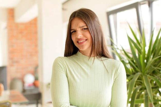 Jonge vrouw die zich angstig, ziek, ziek en ongelukkig voelt en pijnlijke buikpijn of griep heeft
