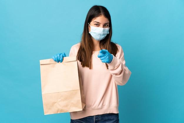 Jonge vrouw die zich beschermt tegen het coronavirus met een masker en een boodschappentas vasthoudt die op een blauwe muur wordt geïsoleerd, wijst de vinger naar je met een zelfverzekerde uitdrukking