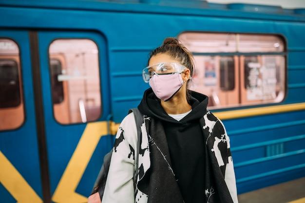 Jonge vrouw die zich bij station in medisch beschermend masker bevindt