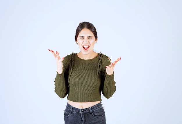 Jonge vrouw die zich boos voelt en schreeuwt op een witte achtergrond.