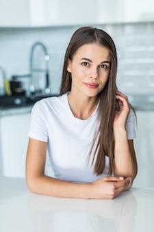Jonge vrouw die zich dichtbij bureau in keuken bevindt.