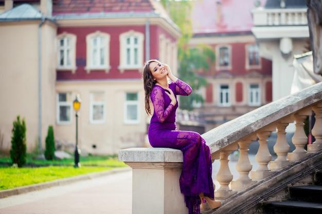 Jonge vrouw die zich dichtbij de muren van een oud kasteel bevindt. schoonheidsmeisje in openlucht in het oude kasteel. mooi model meisje in lange jurk. brunette genieten van reizen. gratis gelukkige vrouw.