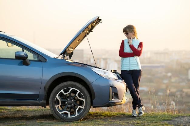 Jonge vrouw die zich dichtbij opgesplitste auto met opgedoken kap bevindt die probleem met haar voertuig heeft. vrouwelijke bestuurder die op hulp naast storingauto wacht.