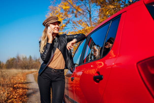 Jonge vrouw die zich door auto bevindt die smartphone op de herfstweg gebruikt. bestuurder stopte auto in forest om te bellen