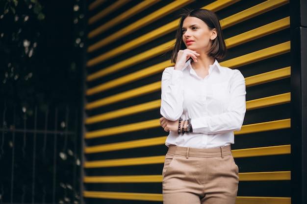 Jonge vrouw die zich door de gele muur bevindt