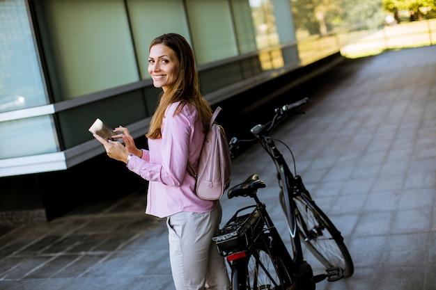 Jonge vrouw die zich door een elektrische fiets bevindt en digitale tablet in stedelijk milieu gebruikt
