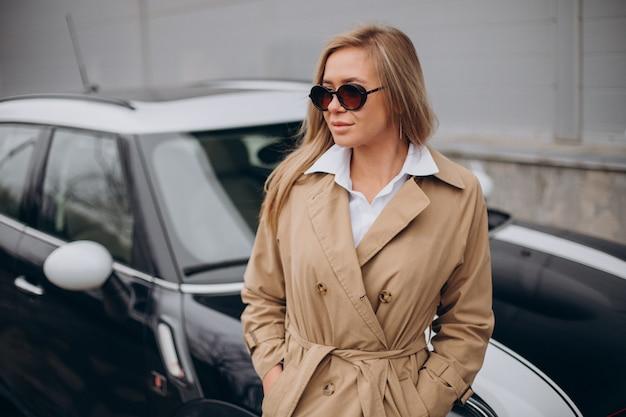 Jonge vrouw die zich door haar auto bevindt