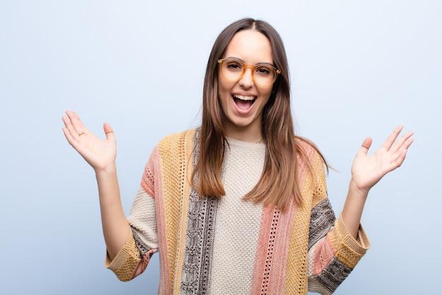 Jonge vrouw die zich gelukkig, opgewonden, verrast of geschokt voelt, glimlacht en verbaasd over iets ongelooflijks op de blauwe muur