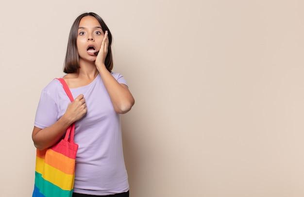 Jonge vrouw die zich geschokt en bang voelt, doodsbang kijkt met open mond en handen op de wangen
