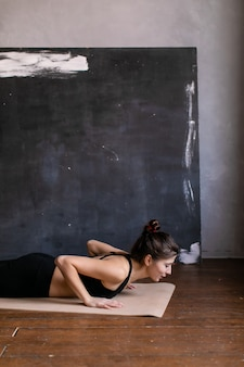 Jonge vrouw die zich in een yogapositie bevindt. meisje die planka at arm's length maken, rekoefening oefenen bij yogales, thuis push-ups doen.