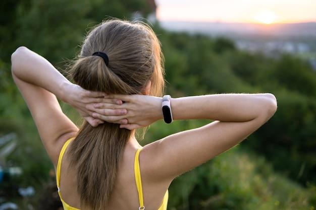 Jonge vrouw die zich in groen gebied bevindt dat van zonsondergang in avondaard geniet. ontspanning en meditatie concept.