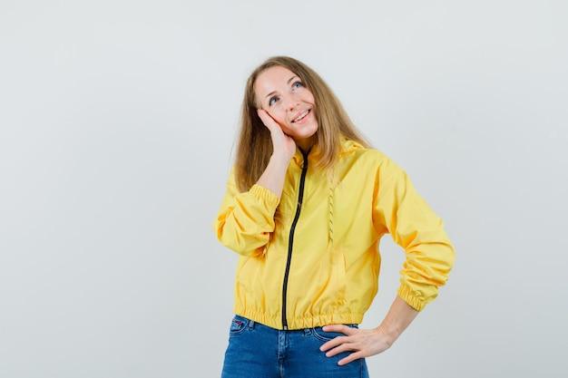Jonge vrouw die zich in het denken gebaar bevindt terwijl hand op taille in geel bomberjack en blauwe jean wordt gehouden en optimistisch kijkt. vooraanzicht.