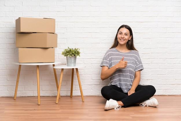 Jonge vrouw die zich in nieuw huis onder dozen geven duimen op gebaar beweegt