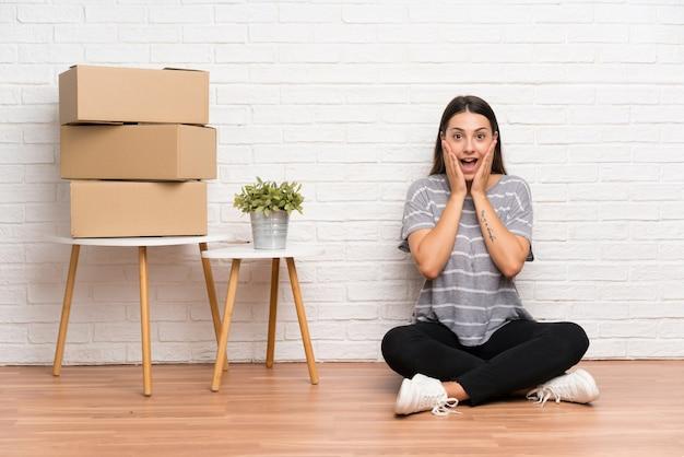 Jonge vrouw die zich in nieuw huis onder dozen met verrassingsgelaatsuitdrukking beweegt