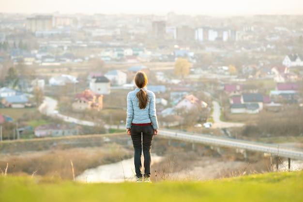 Jonge vrouw die zich in openlucht geniet van stadsmening