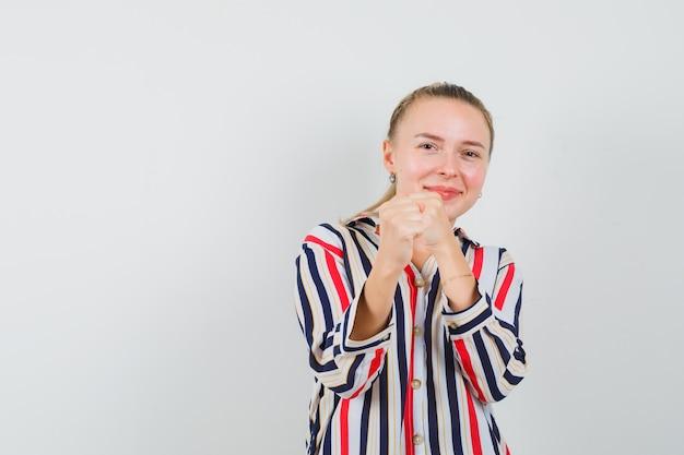 Jonge vrouw die zich in strijdgebaar bevindt en optimistisch kijkt