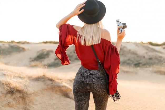 Jonge vrouw die zich in vallei bevindt en op woestijn zandig landschap kijkt